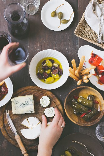 A mini buffet with the cheese platter, red wine, olives, vine leaves stuffed with rice, capers, peppers filled with feta cheese, and dried tomatoes