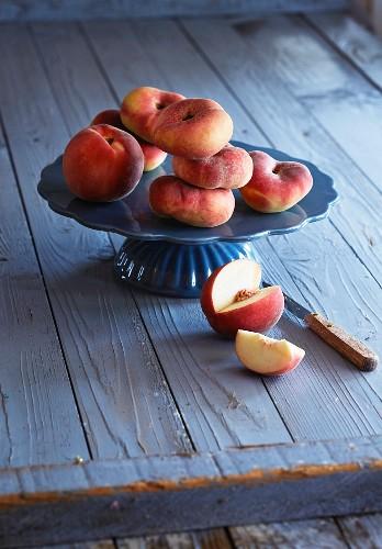 Vineyard peaches and a white peach on a cake stand