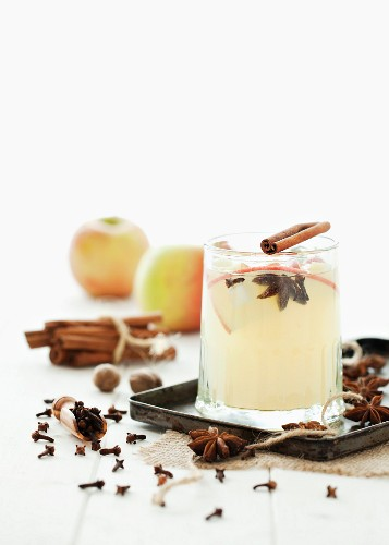 A glass of spiced apple juice on a tray, surrounded by ingredients