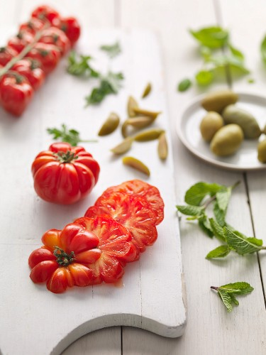 Geschnittene Tomaten und grüne Oliven auf Schneidebrett