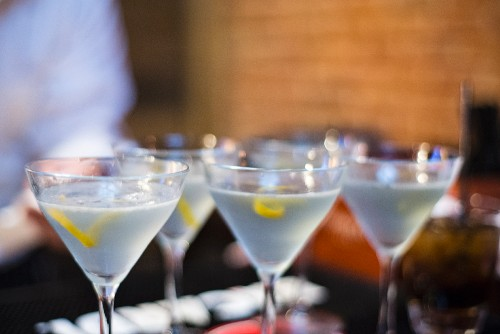 Four martinis with lavender and lemon peel in a bar