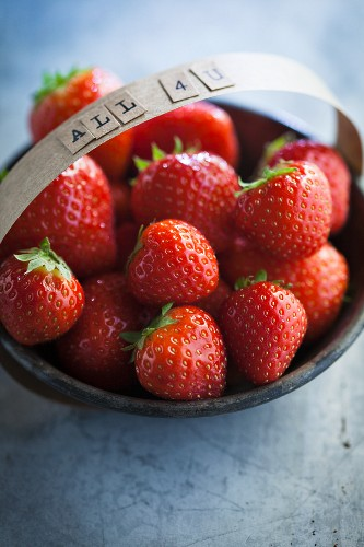 Strawberries in a bowl with the words 'All 4 U' on the handle