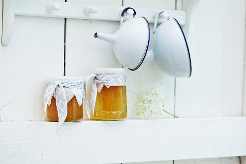 Two glasses of elderberry jam on a kitchen shelf