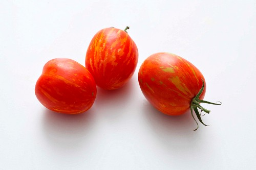 Three red striped tomatoes on a white surface