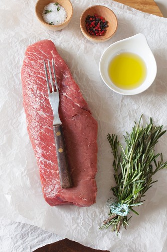 A raw beef steak with spices, oil and rosemary on paper