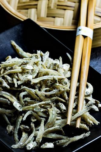 Chirimen (getrocknete Sardellen, Japan) mit Essstäbchen und Bambusgefäß auf schwarzer Platte