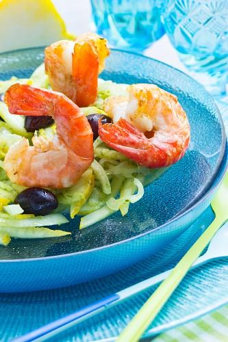 Riesengarnelen auf Zitronen-Fenchel-Salat mit schwarzen Oliven auf türkisem Glasteller
