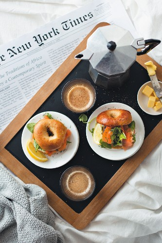 Breakfast in bed with bagels, coffee and newspaper
