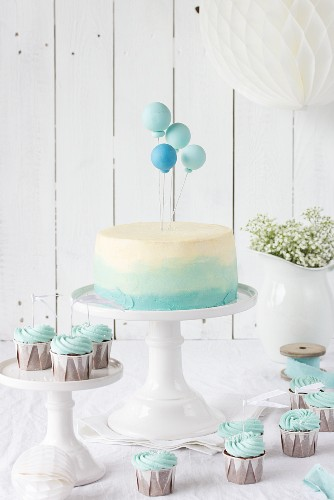 An ombre cake with balloons and chocolate cupcakes