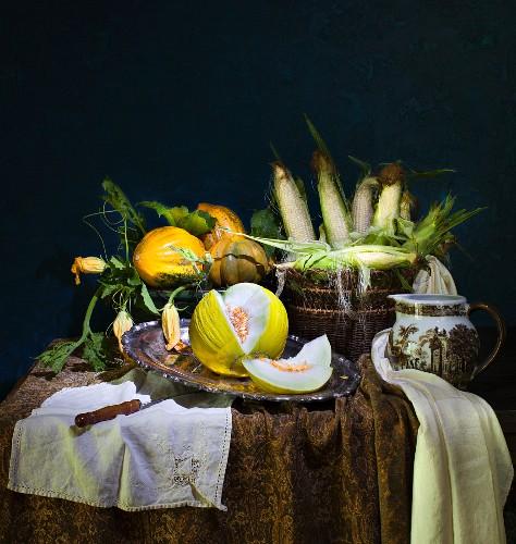 An autumnal arrangement with melons, pumpkins and sweetcorn
