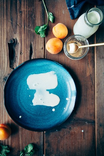 A blue plate with leftover ice cream next to the ice cream ingredients (apricots, cream, sugar and mint)