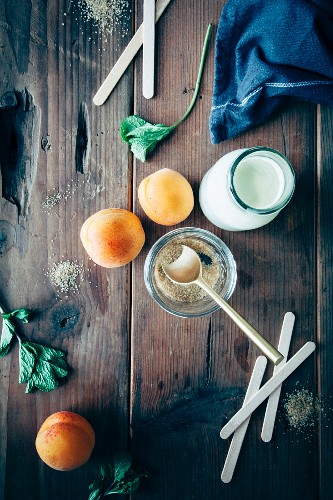 Ingedients for ice creams (apricots, cream, sugar, mint and wooden lolly sticks)