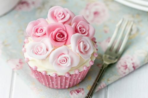 Cupcake mit rosa Zuckerrosen verziert