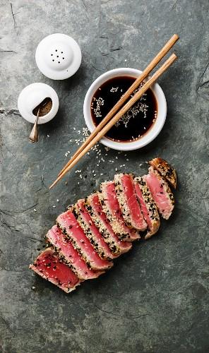 Sliced grilled Tuna steak in sesame and soy sauce on stone slate board