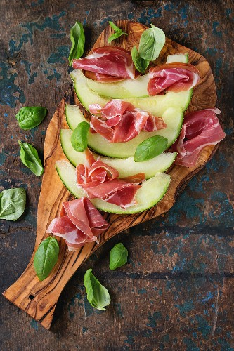 Sliced melon with ham and basil leaves, served on olive wood chopping board