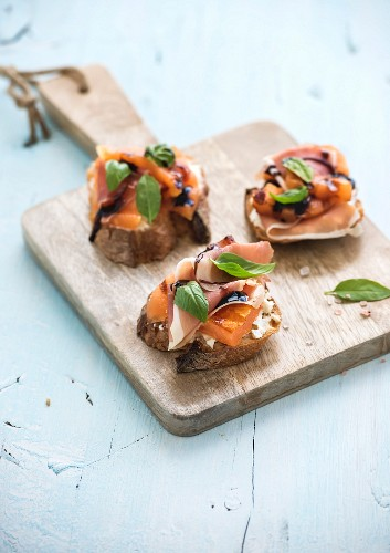 Bruschettas with parma, cream cheese, grilled melon, fresh basil leaves and balsamico on wooden cutting board