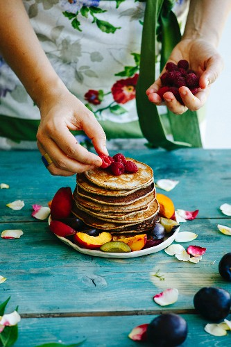 Girl putting raspberries on the top of pancakes