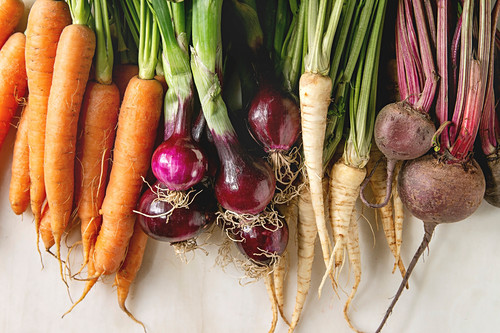 Variety of root garden vegetables carrot, purple onion, beetroot, parsnip with tops over white marble background