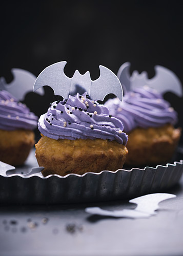 Vegan pumpkin cupcakes with elderberry cream frosting and rice paper decorations for Halloween