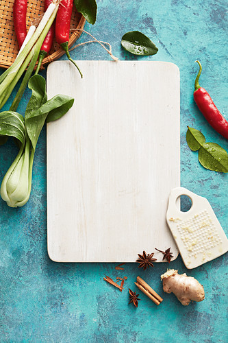 A still life with a cutting board, Asian vegetables and spices