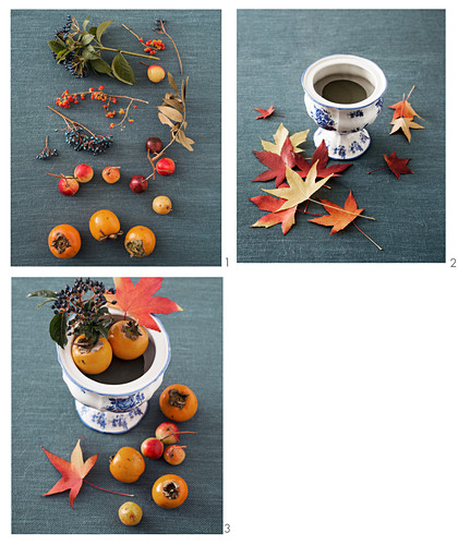 An autumnal arrangement of maple leaves, persimmon, ornamental apples and berry sprigs being made