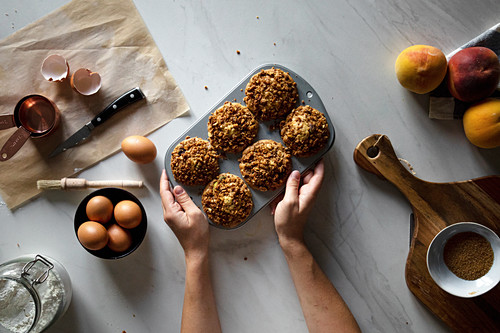 From above crop person holding baking dish with homemade cupcakes on wooden table with arranged eggs with peaches and flour
