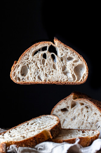 Pieces of tasty fresh bread falling on napkin on table against black background