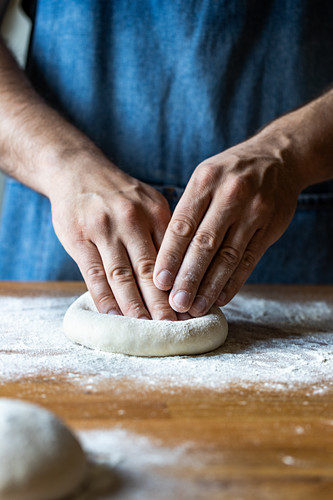 Unrecognizable male in apron flattening soft dough over table with flour while cooking pizza