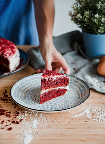 Unrecognizable person putting plate with piece of delicious red velvet cake on table in kitchen