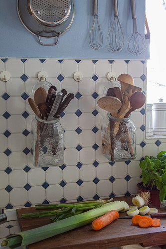 Kitchen utensils stored in swing-top jars hung on wall