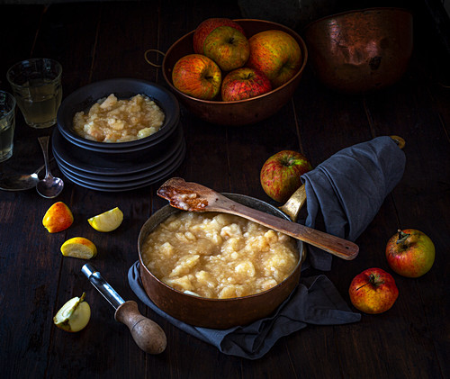 Stewed apples in a pan and bowl with orchard picked apples