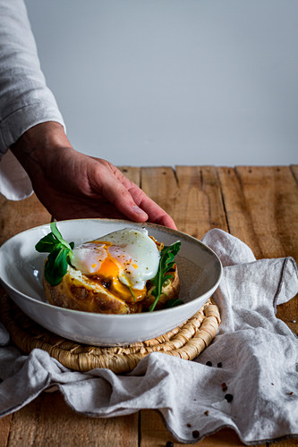 Hand holding dish with fried egg on potato with fried mushrooms, grated cheese and herbs