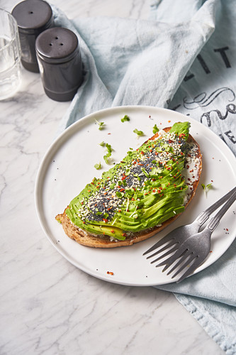 Roasted bread with cream sauce and slices of spiced avocado on white plate with forks
