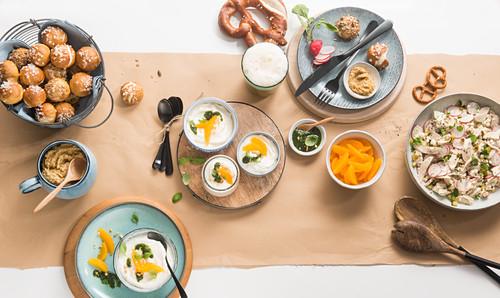 Bavarian supper with a white sausage salad, lye bread bites and a mandarin dessert