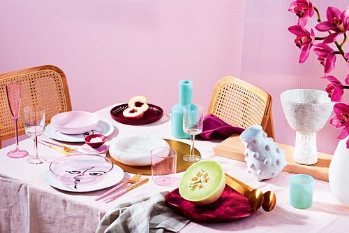 Gedeckter Tisch in Rosa mit Melone und Pfirsich