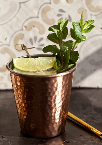 A copper cup with a ginger ale, lime and mint mocktail