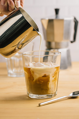 Unrecognizable barista filling glass of coffee with milk