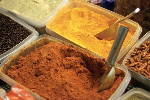 Paprika and turmeric in plastic bowls at the market