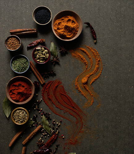 Different kinds of natural aromatic spices placed on dark gray background