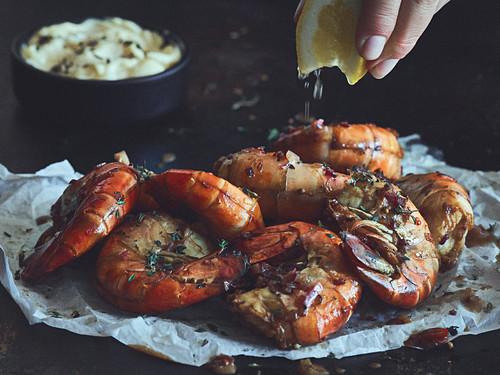 Drizzling smoked king prawns with lemon juice