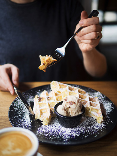 Unrecognizable person using form and knife to cut sweet waffles near bowl of ice cream and cup of coffee