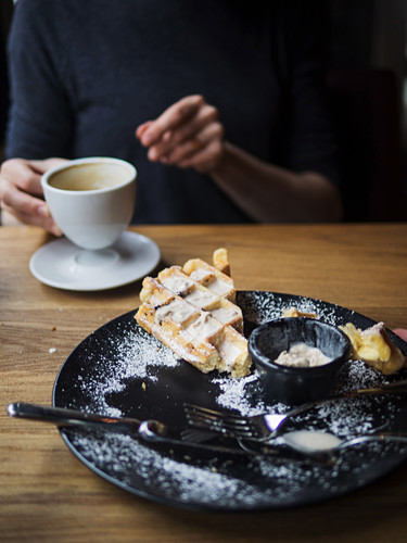 Plate with remains of waffles and ice cream placed on cafeteria table near unrecognizable person drinking coffee