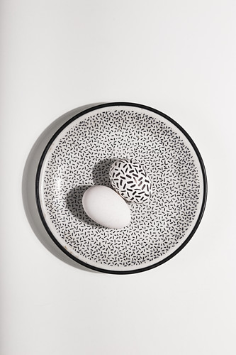 Black and white Easter eggs on a speckled plate