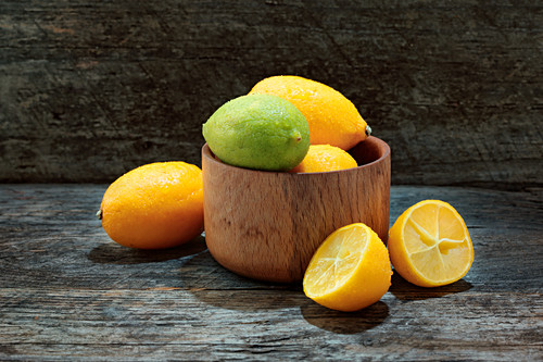 Limequats in a wooden bowl and next to it