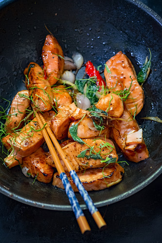 Fried salmon in a wok (Asia)