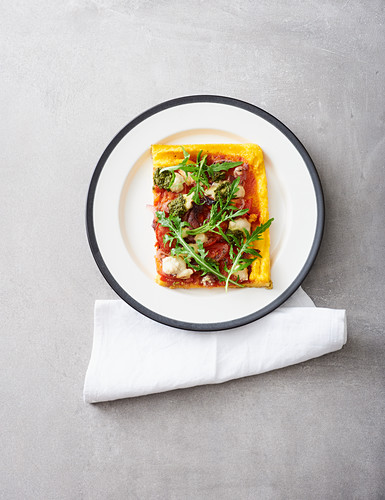 A slice of vegan polenta pizza with tomatoes, onions and pesto