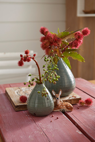 Sprigs of red flowers in vases and deer figurine
