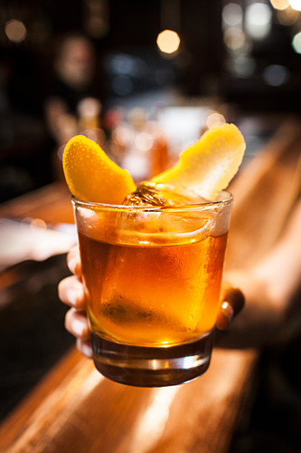 Woman holding Old-Fashioned cocktail