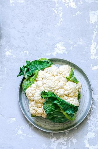 A fresh cauliflower on a ceramic dish