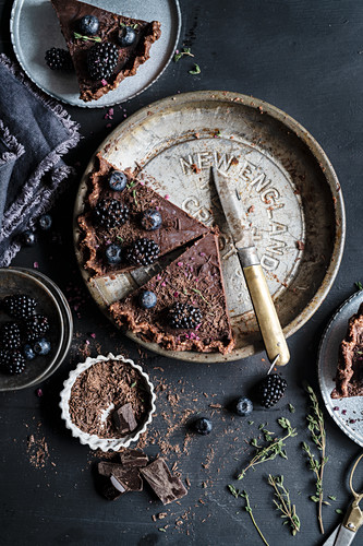 Chocolate tart topped with blackberries and blueberries on a vintage pie plate, sliced